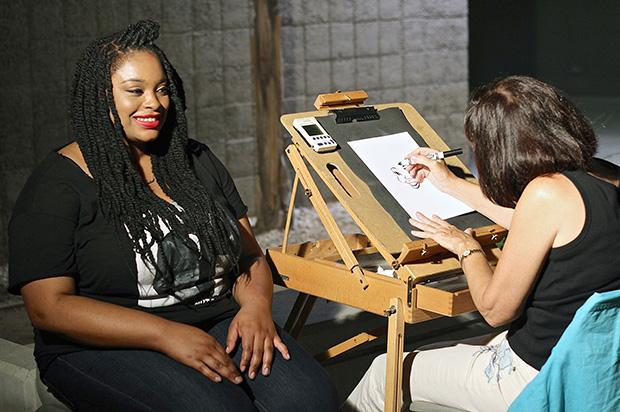 Amber Bernardez, 25, an apparel design and merchandising major, poses for a caricature artist to finish her drawing. Photo Credit: Lucas Esposito / Daily Sundial