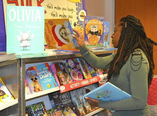 Deanecia Wright, 27, education leadership graduate student, considers which book to purchase for her niece at the Scholastic Book Fair. The book fair will be ongoing until Friday, Oct. 11, 9 a.m. to 4 p.m. Photo credit: Victoria Becerril / Daily Sundial