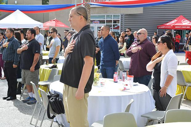 Students and faculty stand to listen to the acapella group, Acasola, sing The Star Spangled Banner. The Veterans Day event honored those in the military. Photo credit: John Saringo-Rodriguez / Photo Editor