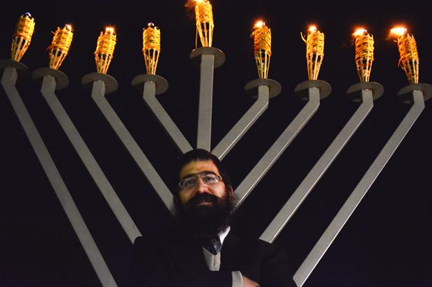 Director of the CSUN Chabad Student Center, Rabi Chaim Brook, in front of a large Menorah on the Oviatt Library Lawn. CSUN celebrated the last night of Chanukah. Photo credit: John Saringo-Rodriguez / Photo Editor
