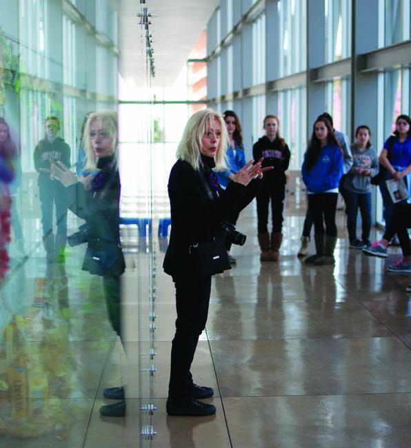 Professor Edie Pistolesi talks to her art 100 students in front of the installation's glass case in Manzanita Hall. Photo by David Hawkins/photo editor