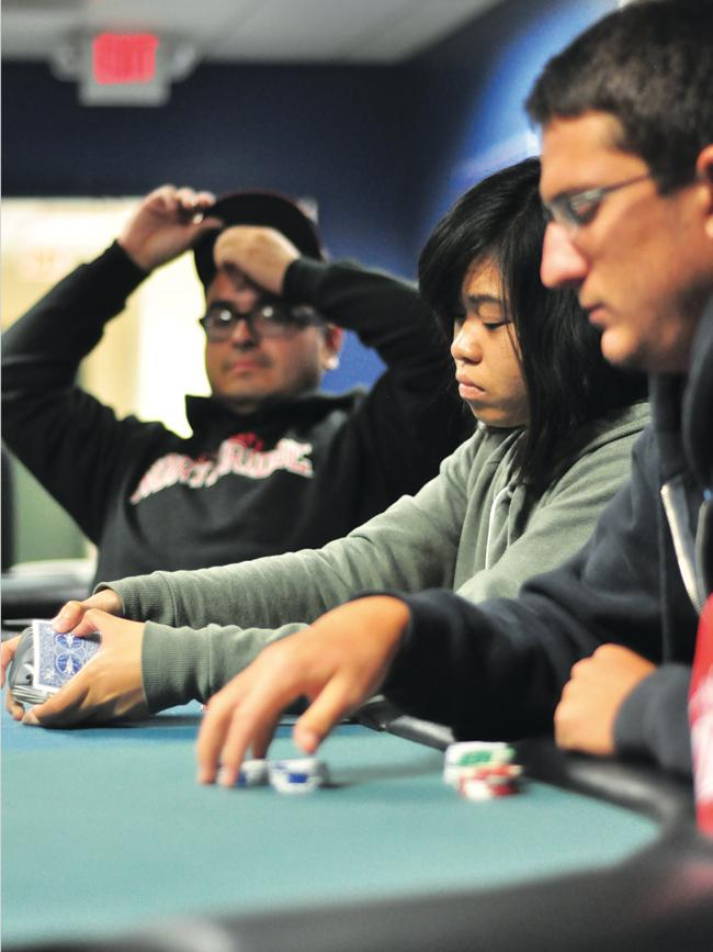 Jose Garay (left), 24, senior mechanical engineering major, Emme Gomez (middle), 18, freshman computer information technology major, and Alex Jones (right), 21, senior marketing major, play a round of Texas Hold 'Em at the first Casino Night in the Games Room of the University Student Union on Tuesday. (Photo Credit: Alex Vejar / Assistant News Editor)