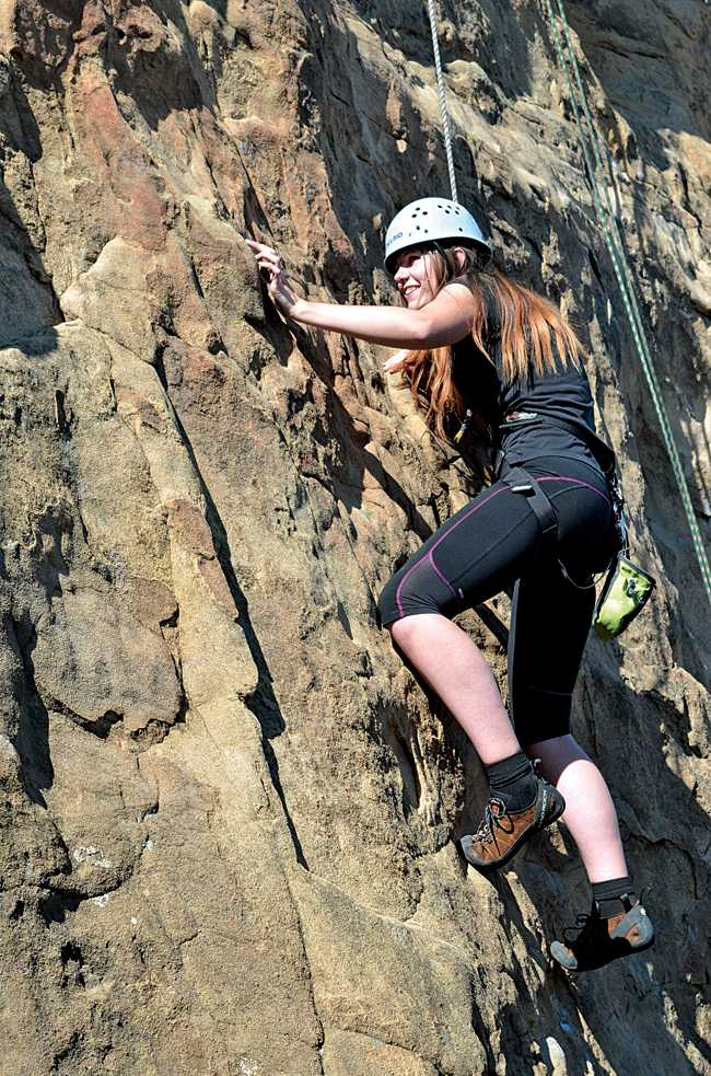 CSUN student Lindsay Barney analyzes her next move up the wall at the beginning of her first climb. (Photo Credit: Christian Akers/Contributor)