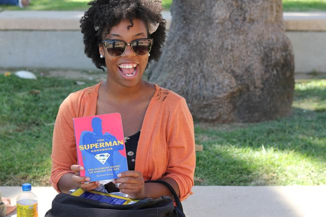 "Brittney Harvey, freshman deaf studies major, shows off her beloved ""How to Be Superman"" book. Photo credit by Brionna Lewis."