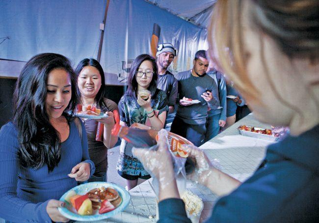 Accounting major, Rubi Barba, pours syrup on elementary education major, Diane De Guzman's pancakes during Final Flip on Wednesday. (Photo Credit: Charlie Kaijo / Senior Photographer)