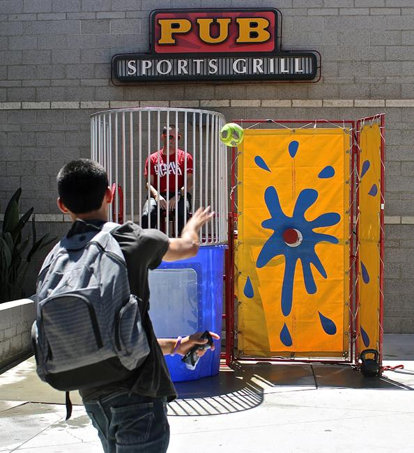 The dunk tank was among the many attractions of CSUN's Matafest. Saqib Bahadar, 21, a senior computer information technology student, attempts to strike the target in order to dunk Jeremy Hamlett, event organizer and USU commercial services manager, Thursday, at Plaza del Sol. Photo Credit: Lucas Esposito /  Senior Photographer