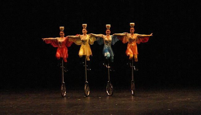 Cirque Peking performers spinning plates on their heads while balancing on unicycles. Photo Credit: Macie Bennett/ The Sundial