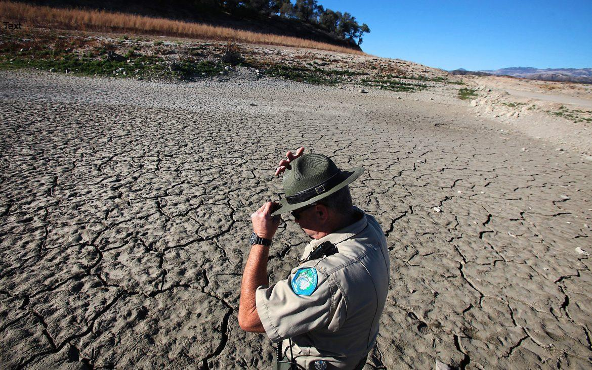 A park ranger stands amidst a dry bay at Lake Cachuma in January 2014. This area was filled with water in 2013. / Courtesy of MTC.