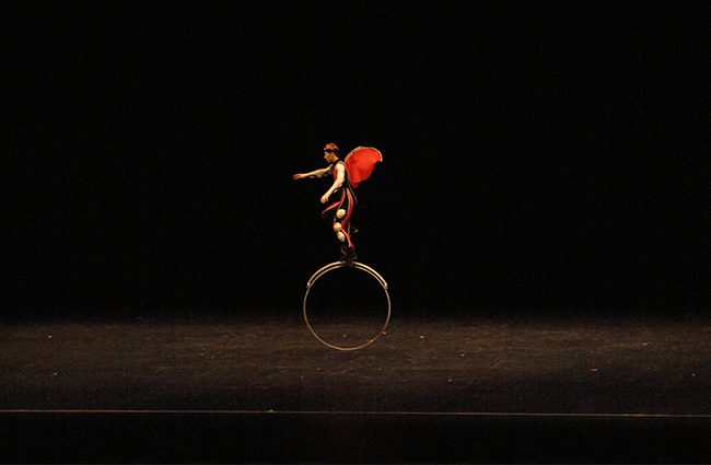Solo performer from the Chinese Acrobat team balances on a tall unicycle. Photo Credit: Macie Bennett/ The Sundial