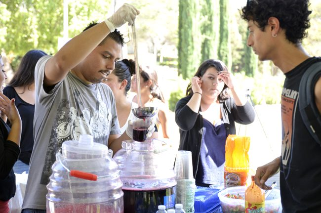 Bryan Solares (left), junior psychology and Central American studies major, serves a drink to Daniel Bonilla (right), junior CTVA major during the EOP 45th celebration event on Sept. 16 on the Matador Bookstore lawn at CSUN. Photo Credit: Alex Vejar/ The Sundial