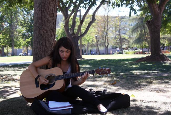 Andrea Aguila, Freshman and Fashion Merchandising Major sits under the trees on her break to practice new songs she has learned in her elective guitar class. Photo Credit: Rasta Ghafouri/ The Sundial