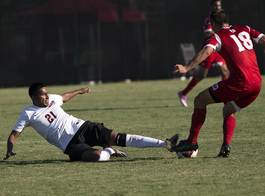 Freshman Kevin Martinez tries to win over the ball with a slide tackle for the Matadors during the team's Sunday scorcher against the Bradley Braves. The Matadors pulled out a 1-0 win in the second overtime period. Photo credit: Trevor Stamp/The Sundial
