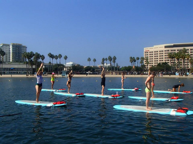 Students try to balance on paddle boards during yoga class in the Marina. Photo courtesy of Yogaaqua.