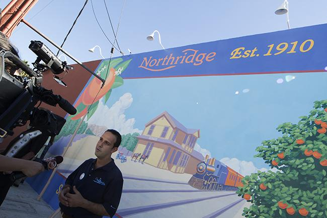 Los Angeles City Council Member Mitchell Englander answers questions for the press in front of a newly unveiled mural on the side of