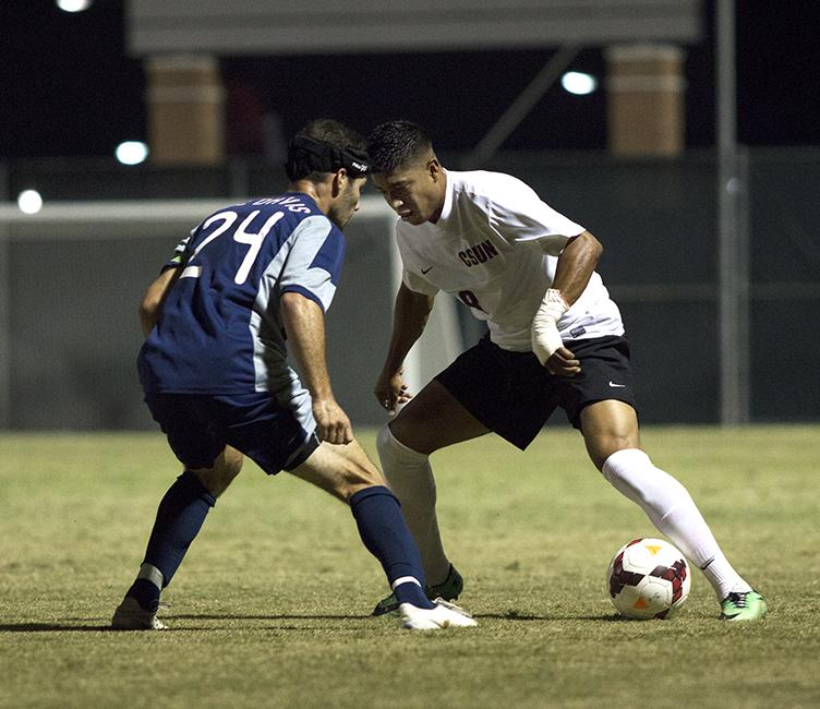 Redshirt senior Edwin Rivasgoes head-to-head with UC Davis' Brian Ford in Saturday night's match-up. After a tense match that bled into overtime, the Matadors tied the Aggies 0-0. Photo Credit: Trevor Stamp/Senior Photographer