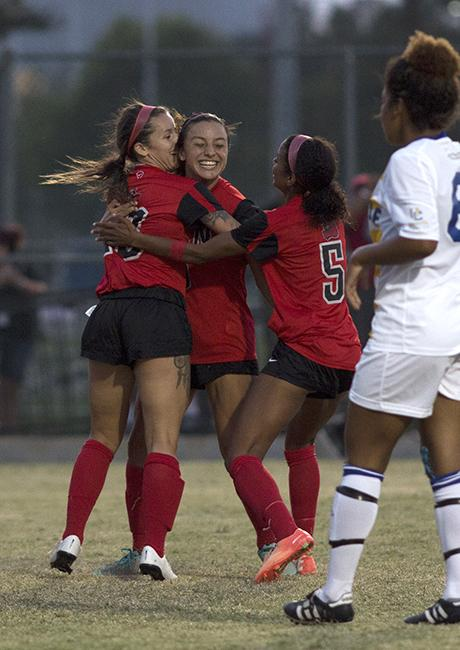 Sophomore Cynthia Sanchez (center) is embraced by junior Lyndsey Preston (left) and sophomore Camille Watson after Sanchez scored the only goal of the match against the UC Riverside Highlanders on Oct. 12, 2014. After winning their Sunday evening match against the Highlanders, the Matadors now have a 3-0-0 record in the Big West Conference. Photo credit: Trevor Stamp/ The Sundial
