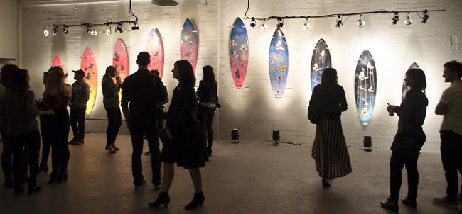People gathered around the real life sized surfboard art by Rob Machado at Flood Magazine Gallery in Los Angeles, Calif., on Jan. 29, 2015. (File Photo / Raul Martinez / The Sundial)