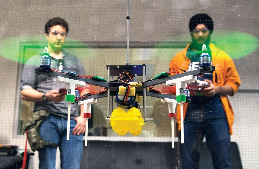 Jeremy Friedman, 24, a mechanical engineering student, and Karanvir Panesar, 20, a computer engineering major, test a remote controlled quad-copter on Feb. 3 in Jacaranda Hall. Photo Credit: Trevor Stamp / Multimedia Editor