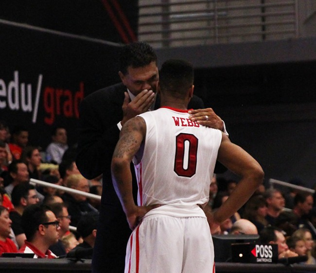 Head coach Reggie Theus has a private conversation with freshman Taelin Webb in the second half of the Matadors' matchup with UC Davis on Feb. 7, 2015. (Trevor Stamp / Multimedia Editor)