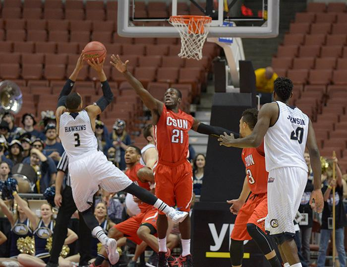 Senior Stephen Maxwell tries to get a hand in front of UC Davis' Corey Hawkins shot during the Matadors' qurater final game on March 12. (Raul Martinez / Staff Photographer