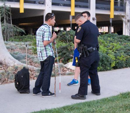 Erick Gallegos, a computer science major, speaks to a CSUN Department of Police Services officer after a man stepped on his cane, breaking it and walked away. Photo Credit: Rose Barraza / Sundial Staff Photo credit: Rose Barraza