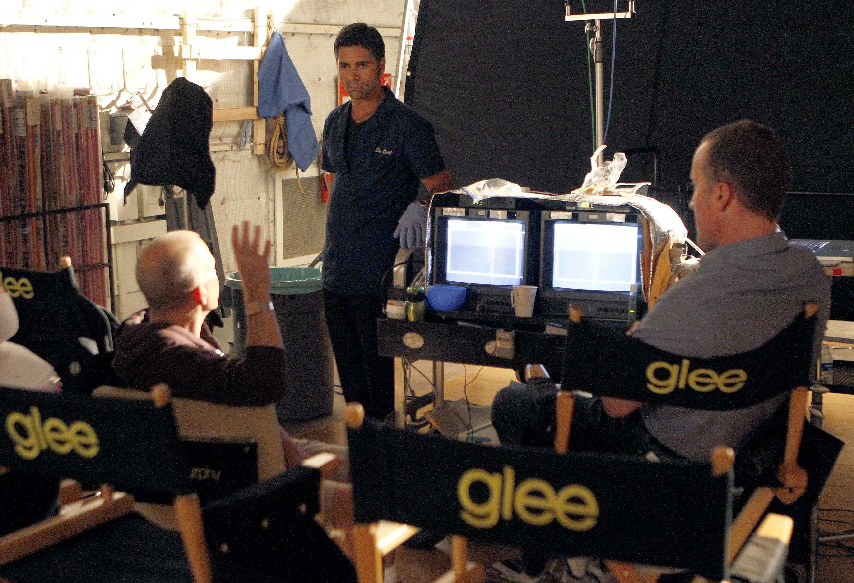 Glee creater Ryan Murphy (seated left) gives a few directs for the scene to John Stamos who guest starred on an episode of