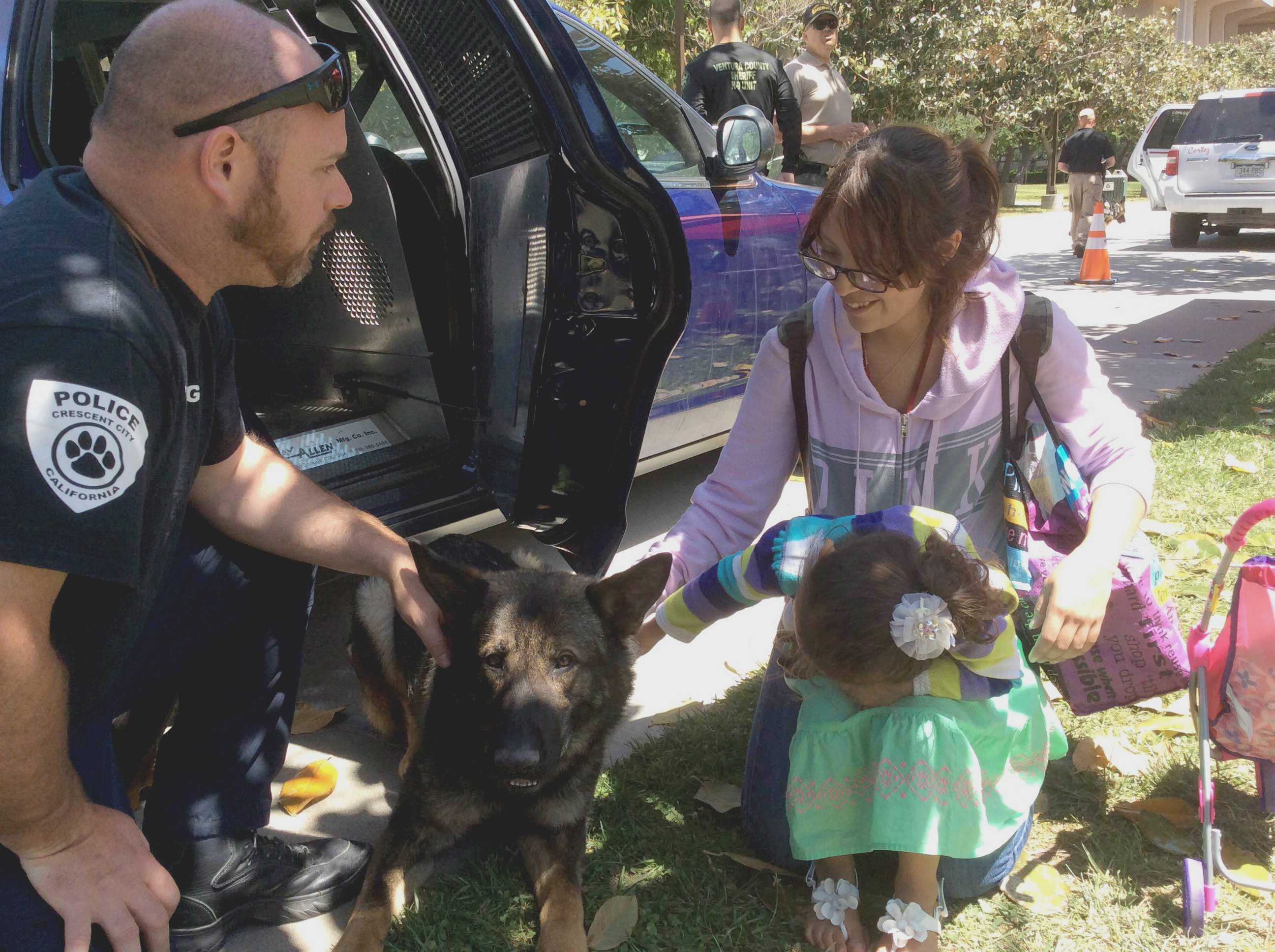 CSUN student Joselyn Cano and her daughter, Emily, 3, pet Django, belonging to Crescent City Police Department officer Aaron King. Photo credit: Michael Arvizu