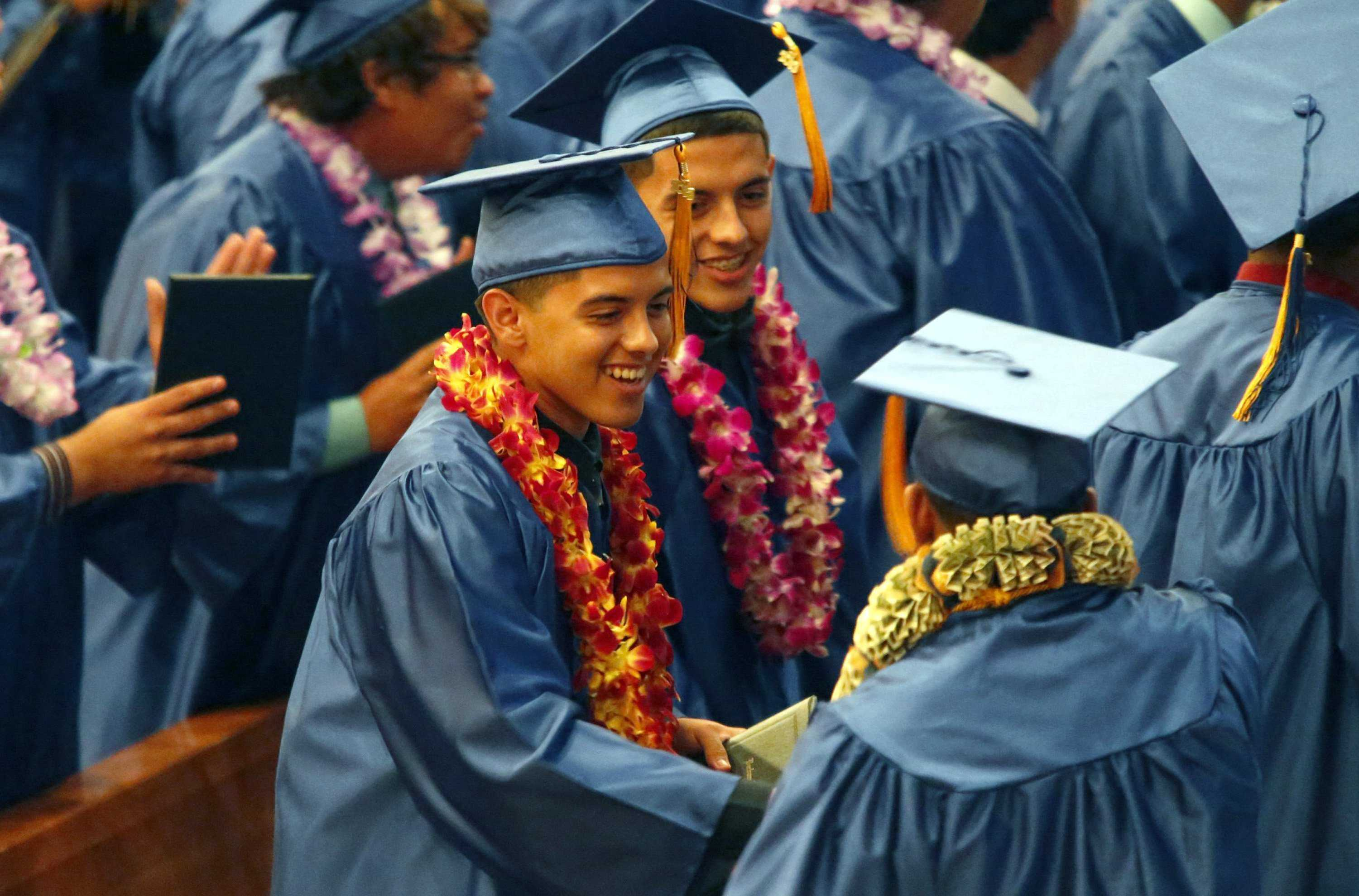 Twin brothers Robert (left) and Ricardo Placensia shake hands with fellow Verbum Dei High School graduates during a ceremony at the Cathedral of Our Lady of Angels in Los Angeles, June 6, 2013. (Don Bartletti/Los Angeles Times/MCT)