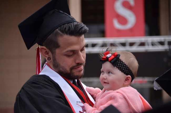 The new CSUN graduate holds an infant in his arms after receiving his Bachelor's Degree on May 16, 2015.