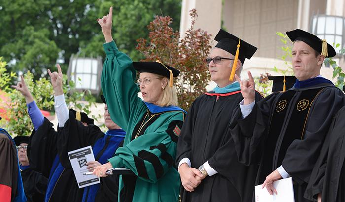 """President Harrison and staff sing along the """"Hail to the Matadors"""" alma mater and fight song."""