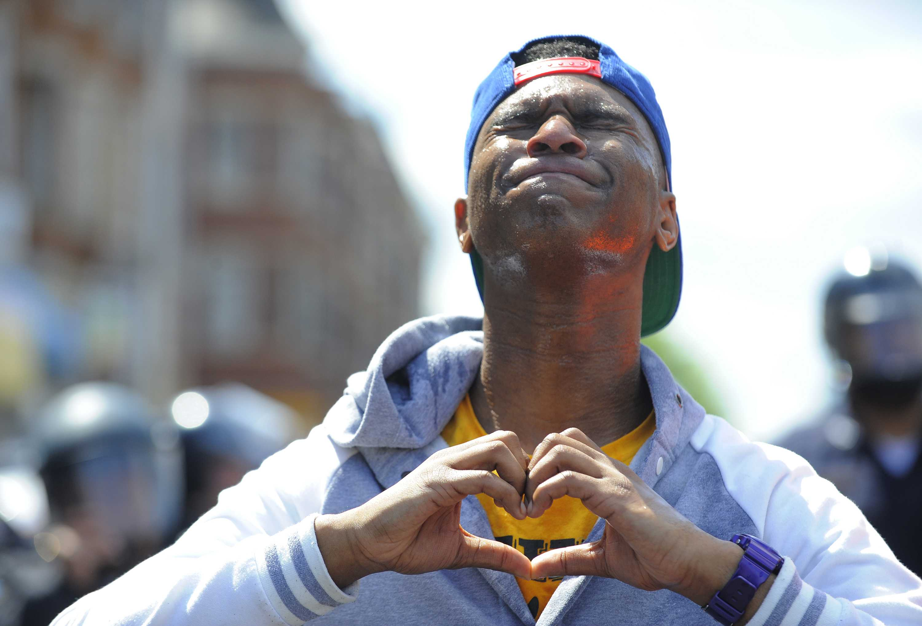 Devante Hill makes a heart with his hands after he was hit with pepper spray after someone threw a bottle at police on Tuesday, April 28, 2015, in Baltimore. (Lloyd Fox/Baltimore Sun/TNS)