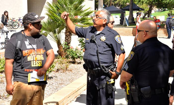 CSUN+police+officers+tell+Diego+Massimo+%28left%29+that+his+group+%22Stop+Mass+Incarceration%2C%22+needs+a+permit+to+distribute+literature+on+campus.+Photo+credit%3A+Leni+Maiai