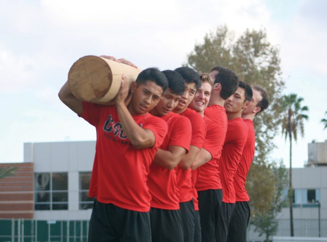 Nic Alegrado leads his squad in lifting a 280 pound log as part of their Navy SEAL training. (Leni Maiai / The Sundial)