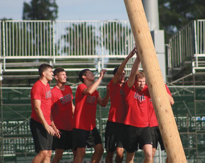 Redshirt freshman Jakob Karlsson is assisted by his teammates in flipping a 280-pound log. (Leni Maiai / The Sundial)
