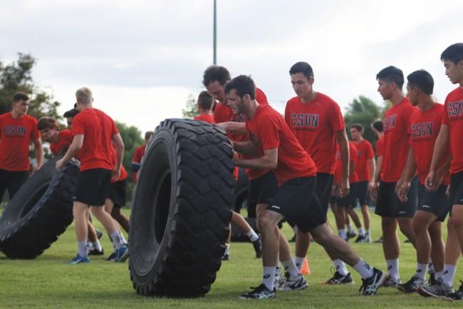 Travis O'Gorman and Rupert Scott race to flip their tire to avoid punishment. (Leni Maiai / The Sundial)