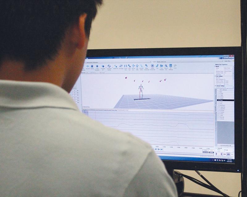 Kyle Salcedo, senior kinesiology major, uses the Cortex Motion Analysis program to analyze how much force is being exerterd by Raman Sharma. Photo credit: Daniel Velarde