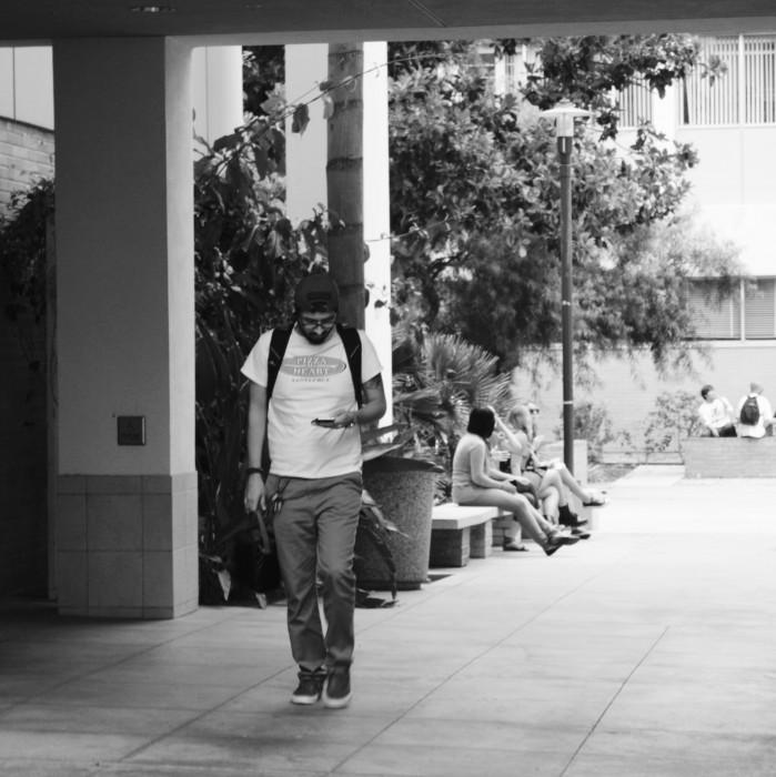 A student walking on campus while using his cell phone.