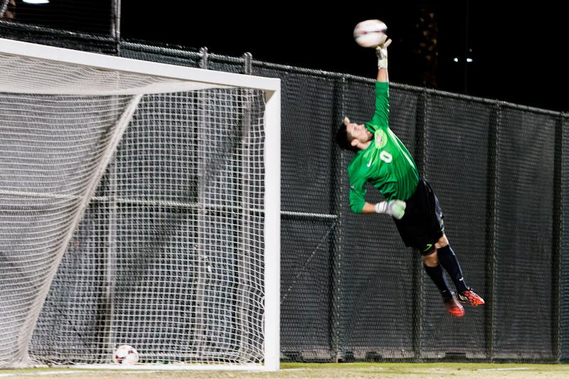 CSUN goalkeeper Adam Hobbs blocks opposing soccer ball.