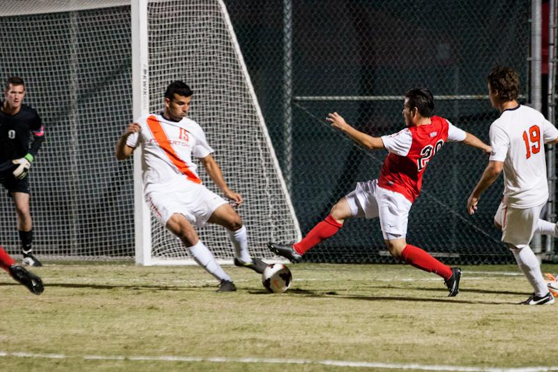 CSUN soccer player attempts to steal ball away from opponent.