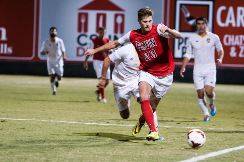 CSUN student (number 23) strays ball away fro, opponent.