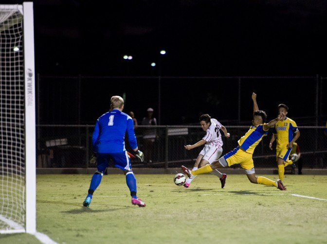 CSUN soccer players (red and white) play hard to keep ball away from the Gauchos (blue and yellow).
