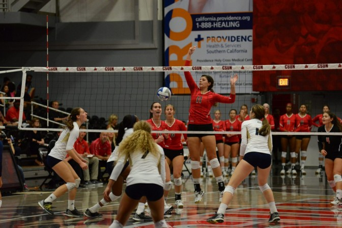 CSUN volleyball player spikes ball over net in an attempt for Long Beach State to fail to return it.