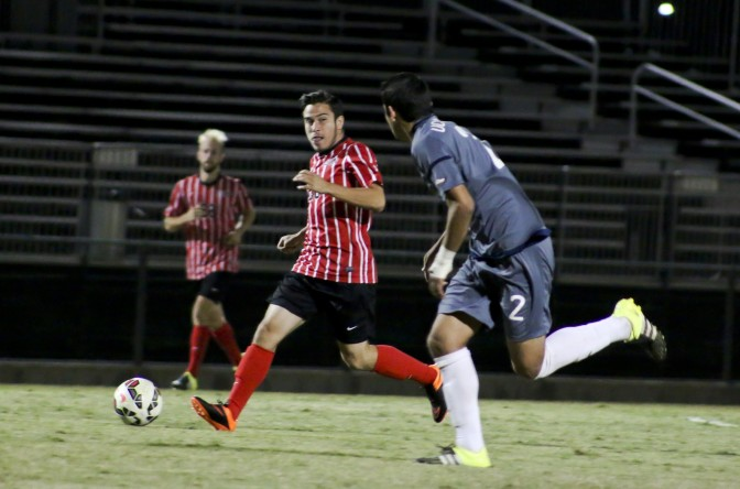 CSUN student (red) strives to keep soccer ball away from opponent (navy).