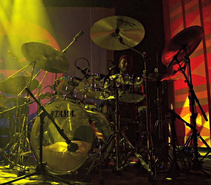 The drummer of thundercat preparing to play on his drum.