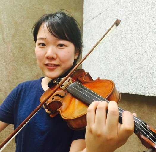 Tang posing in a practice room with her violin.