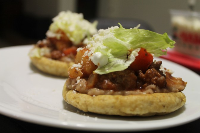 A finished sope topped with meat, lettuce, tomatoes and sour cream.
