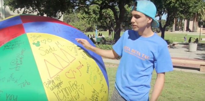 A Beta Beta Tal fraternity member explains the reasoning for the multi-colored ball that is singed by donating CSUN students for a charity for The Children's Hospital of L.A.