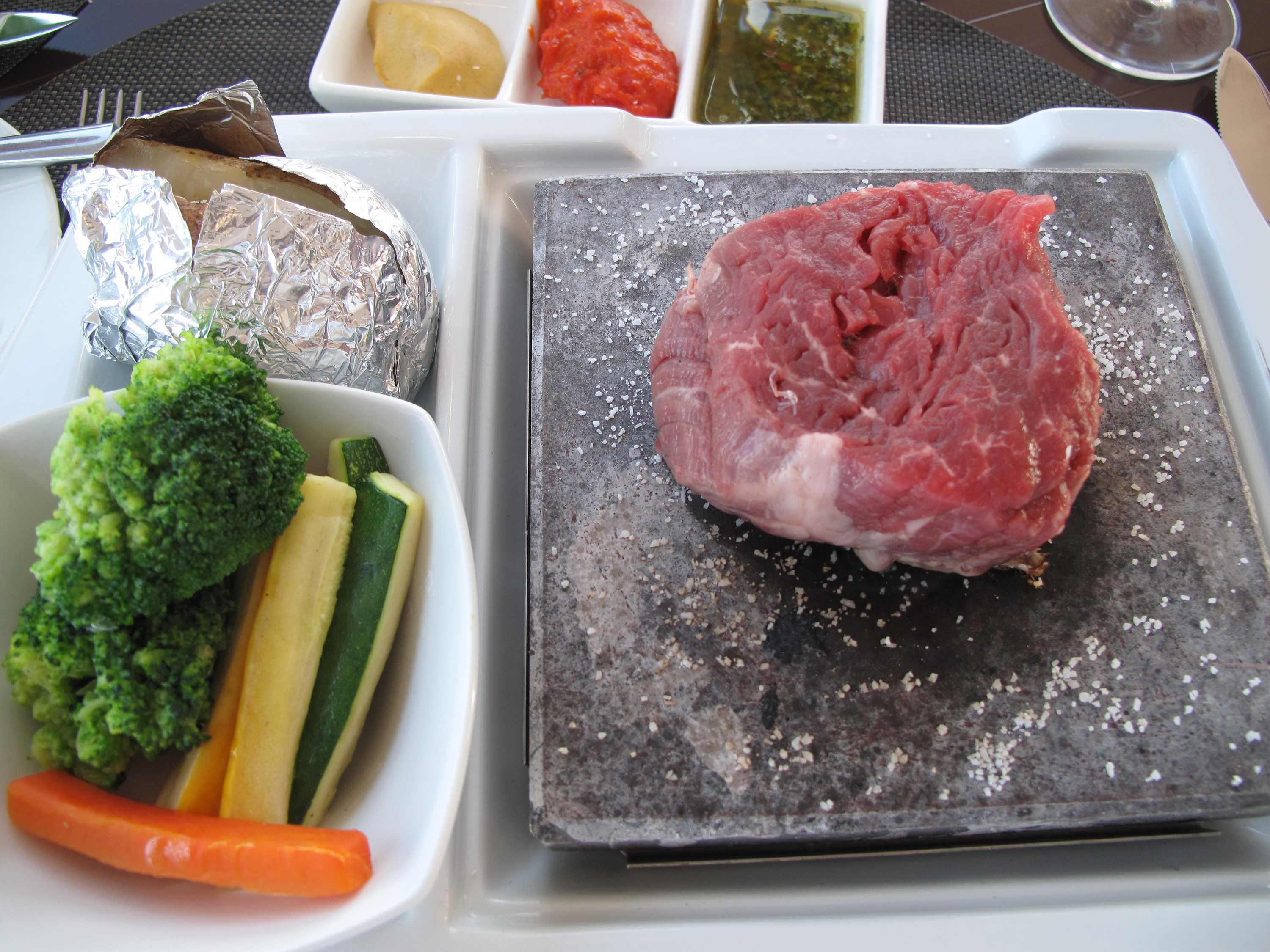 A picutre depicting a piece of raw meat. Surrounded by various vegetables and other foods.