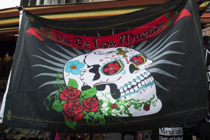 "A flag that advertises ""Dia de Los Muertos"" (Day of the Dead). This holiday is celebraed on November 1 and November 2."