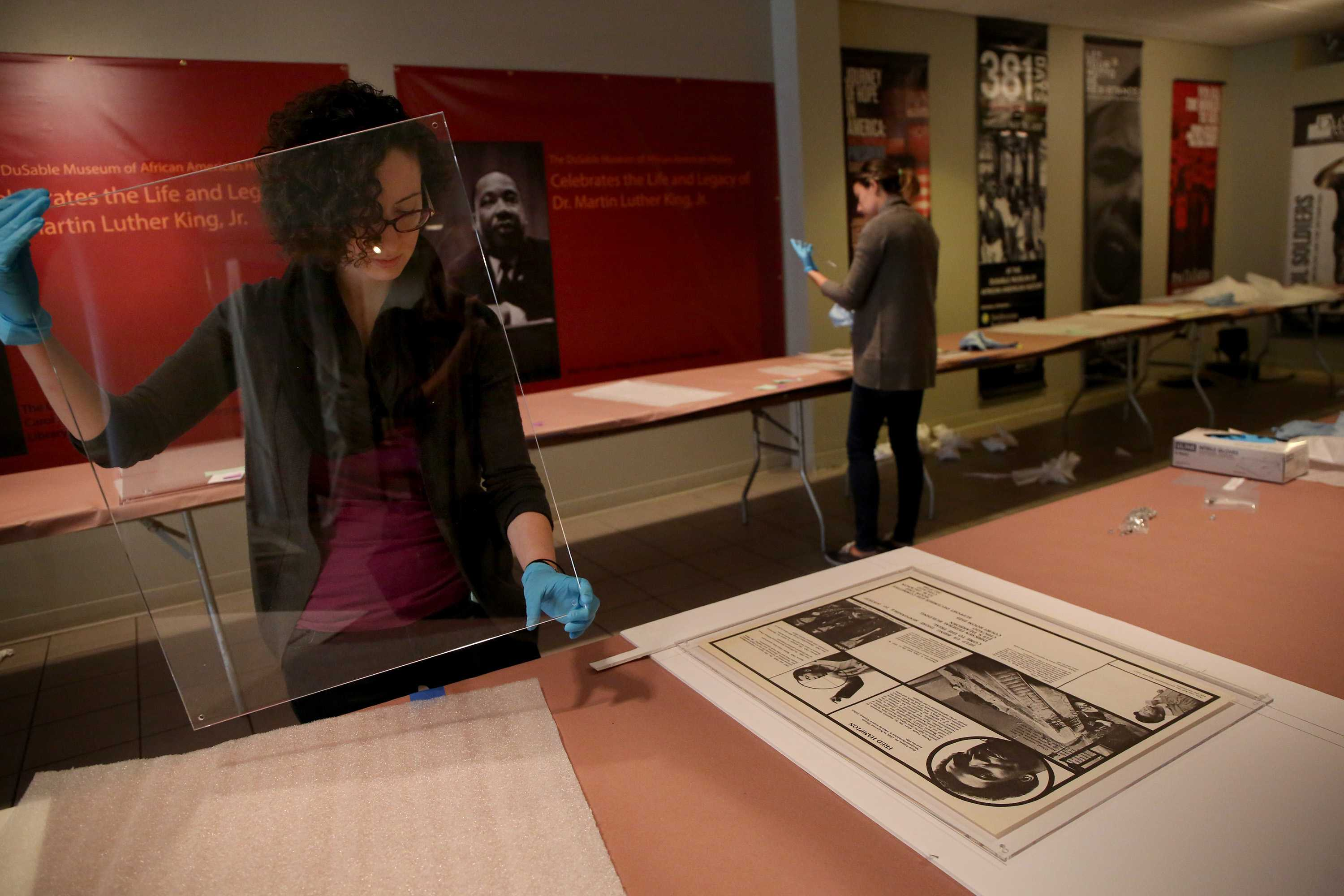 Workers set up display for African American art.